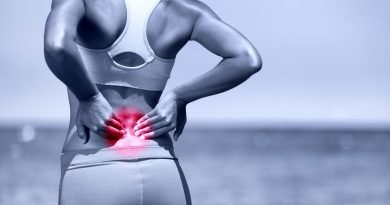 34943050 - back pain. athletic running woman with back injury in sportswear rubbing touching lower back muscles standing on road outside.