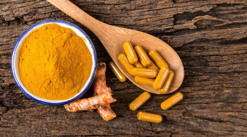 the turmeric powder , capsule and roots curcumin on wooden plate
